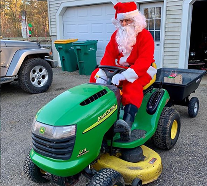 A man dressed up as Santa Claus sits on a tractor in the driveway.