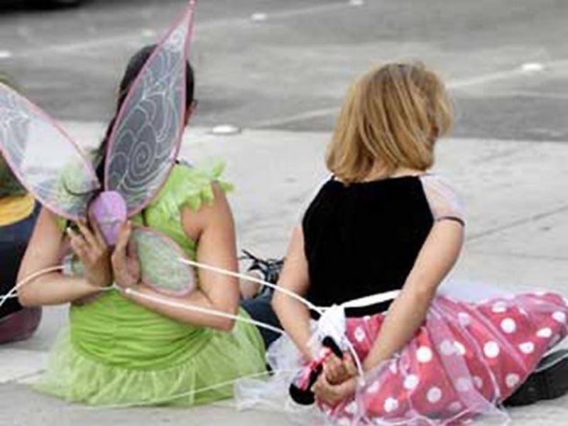 Two women dressed as Tinkerbell and Minnie Mouse sits on the sidewalk in handcuffs.