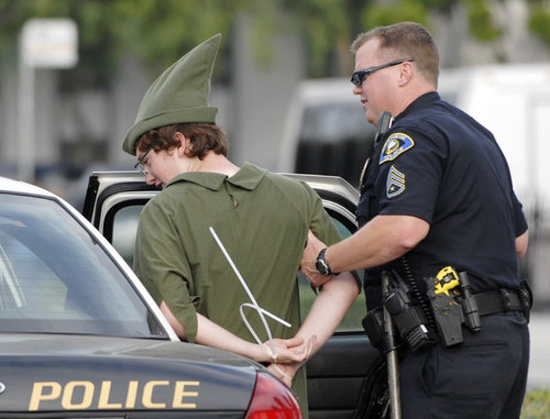 Someone dressed as Peter Pan is escorted into the back of a cop car.