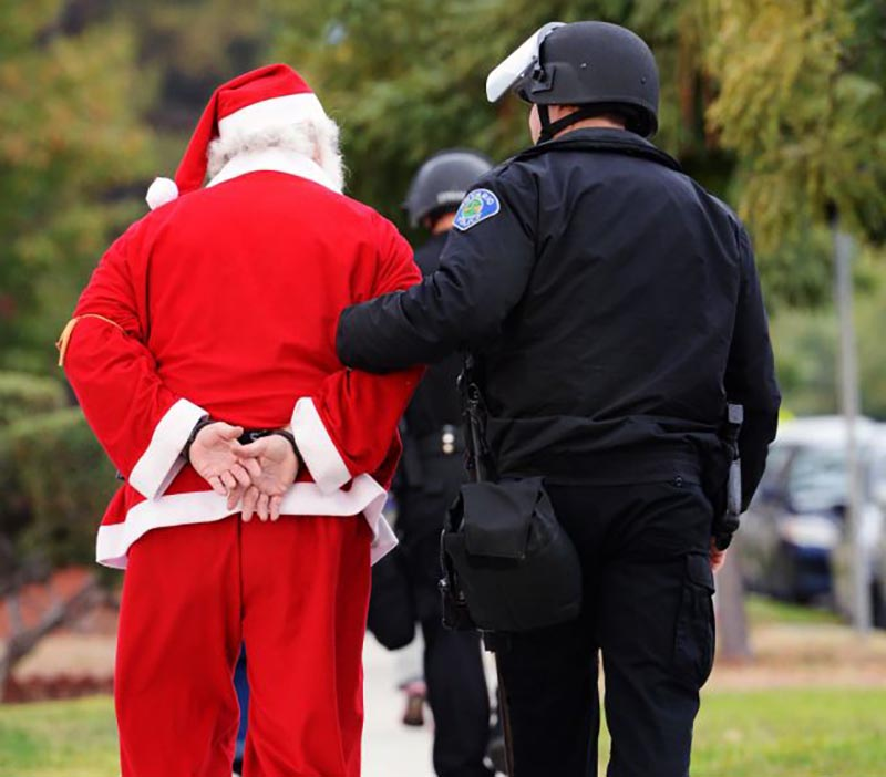 An officer escorts a handcuffed man who is dressed as Santa Claus.