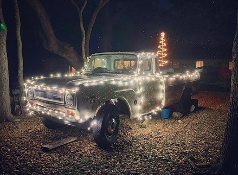 A truck is covered with Christmas lights.