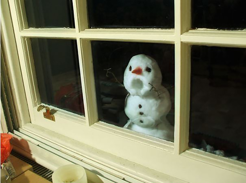 A snowman looks like it's yelling and banging on a window.