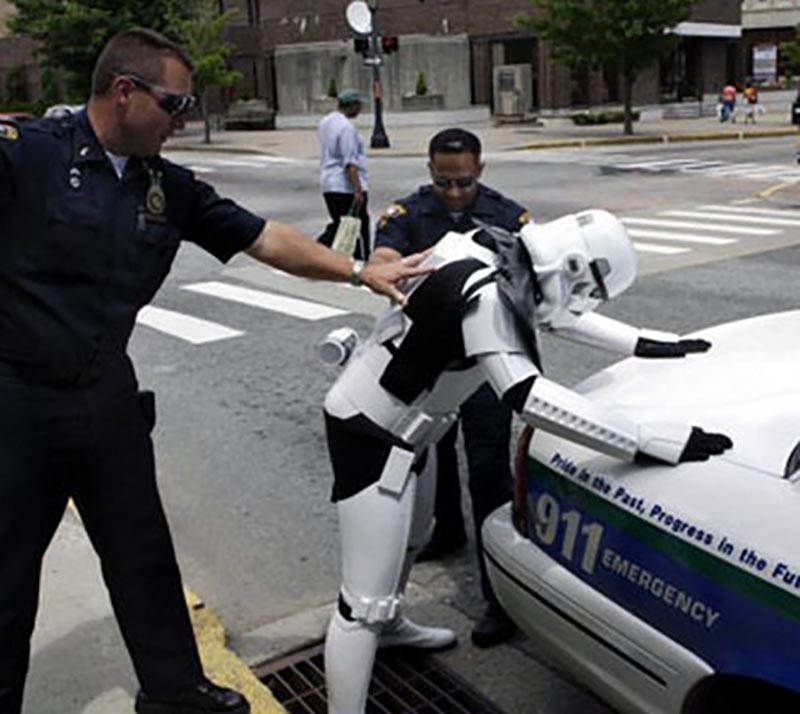 A person in a stormtrooper costume is leaned over a cop car by police.