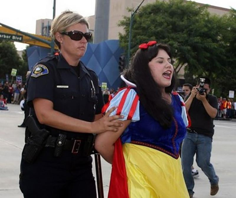 A woman dressed as Snow White has an open mouth while being escorted in handcuffs by a police officer.