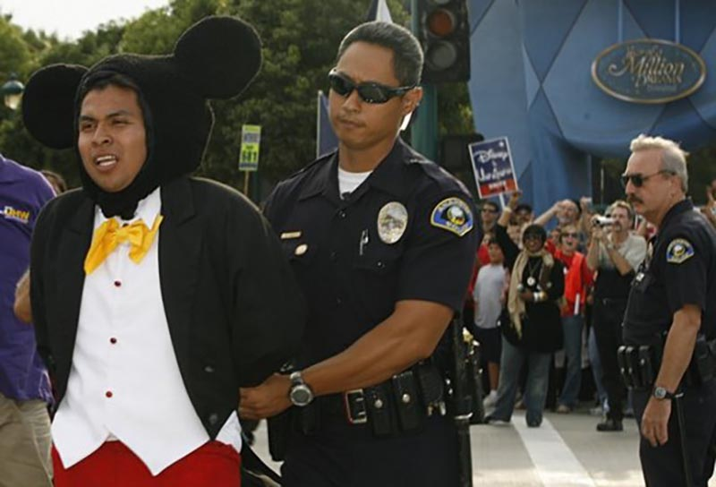 A man dressed in a Mickey Mouse costume is escorted by an officer while in handcuffs.