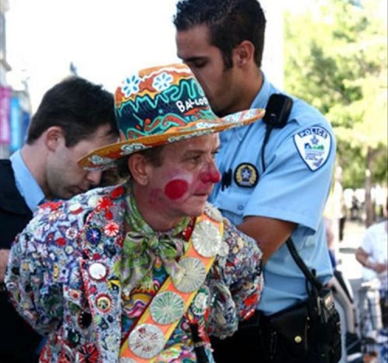 A man dressed as a clown in handcuffed by an officer.