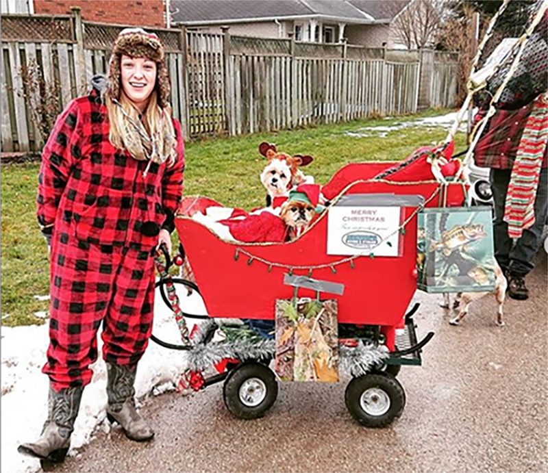 A woman in pjs and cowgirl boots stands next to a santa sleigh on wheels that holds two dressed-up dogs.