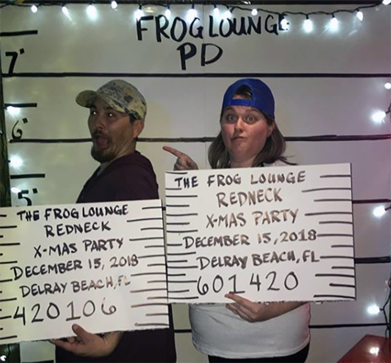 A man and woman make silly faces while posing for a fake mug shot.