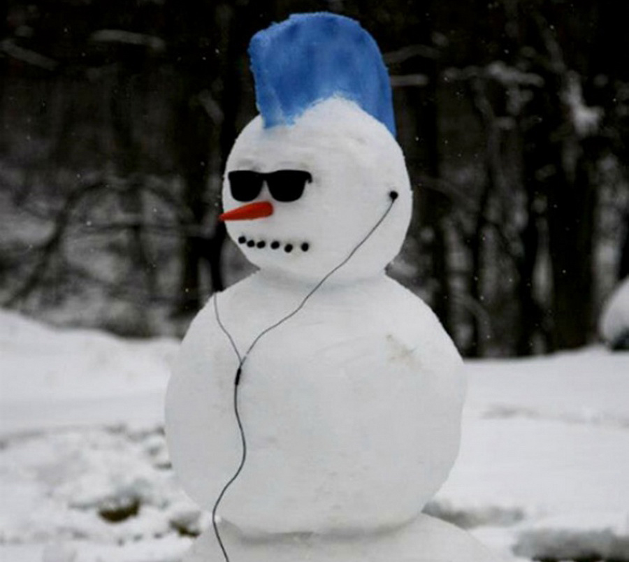 A cool snowman has a blue mohawk, sunglasses, and ear pods.