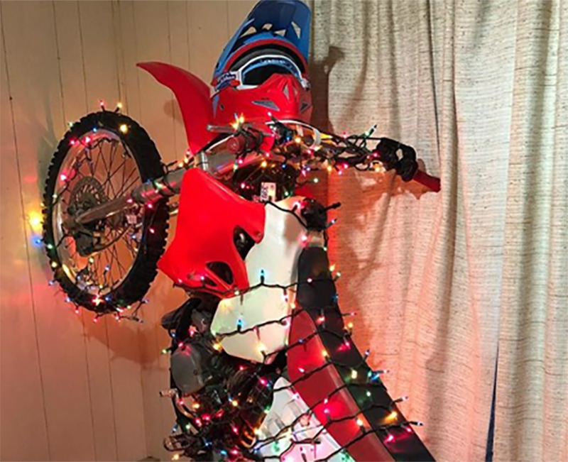 A dirt bike is leaned vertically against a wall and wrapped in Christmas lights.