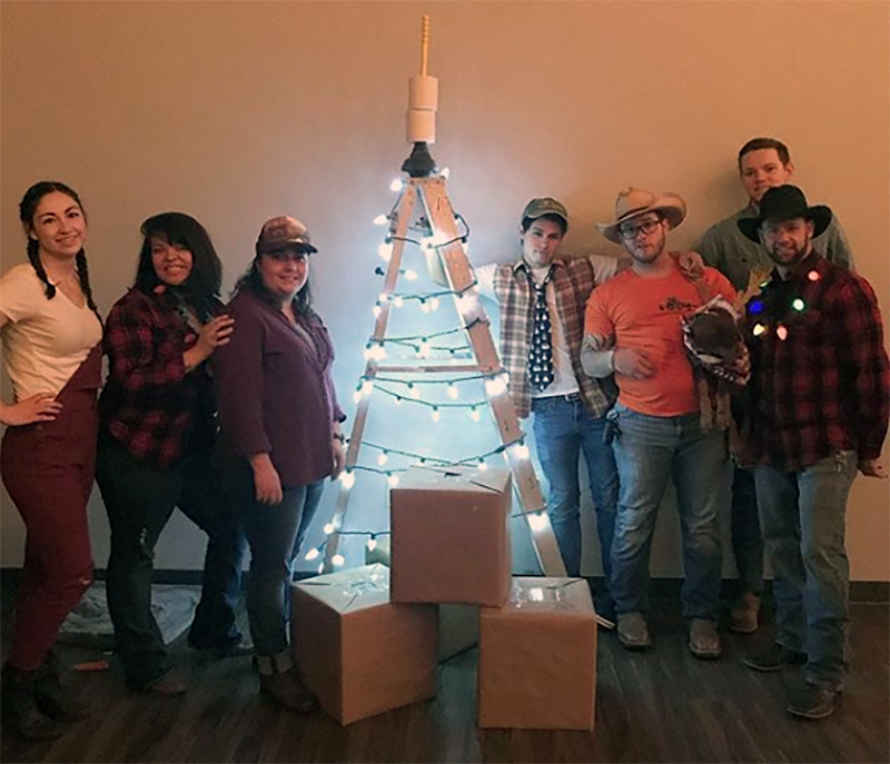 Friends pose next to a makeshift Christmas tree topped with a plunger.