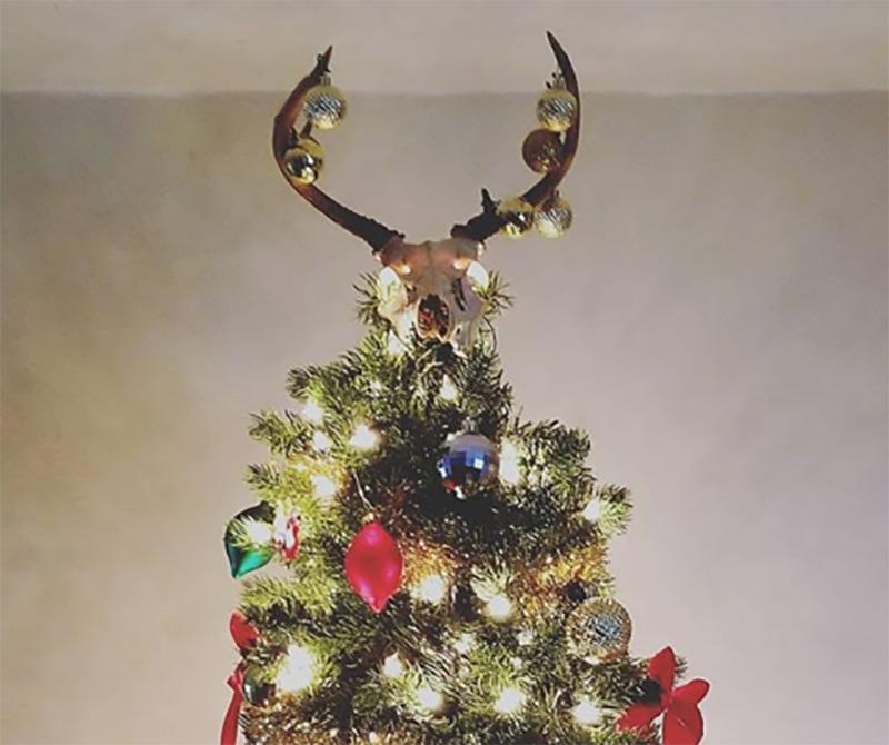 The skyll of a hunted animal sits on top of a Christmas tree.