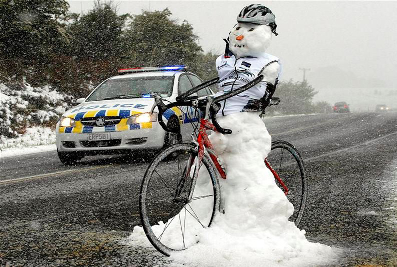 A snowman dressed in  a helmet and vest rides a bicycle.