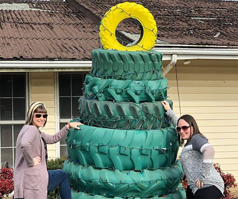 Two woman pose next to a stack of green tires topped with a yellow tire to look like a Christmas tree.