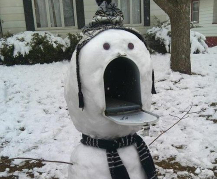 A snowman is built around an open mailbox, which it uses as a mouth.
