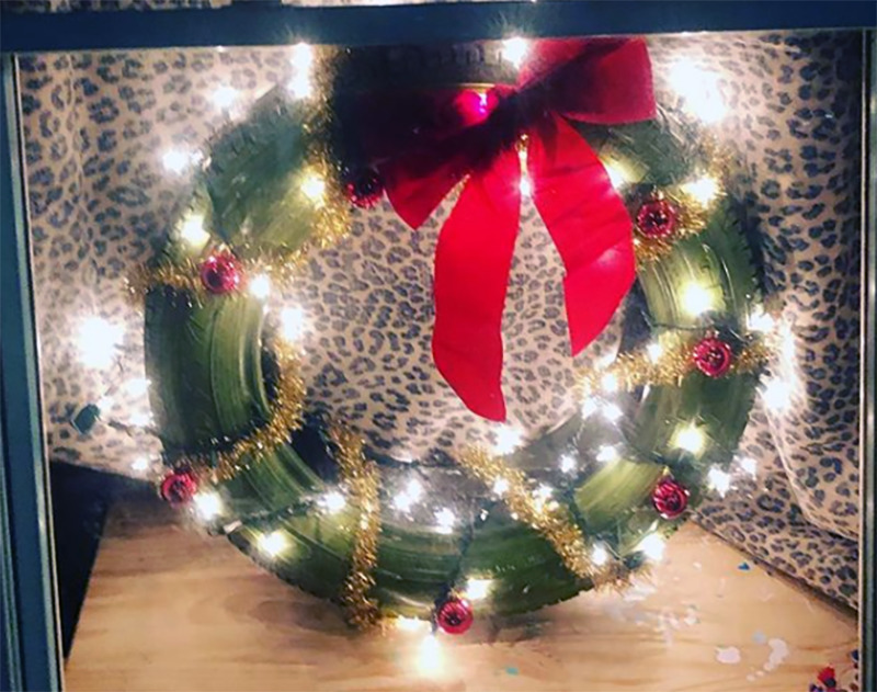A tire is decorated as a wreath and placed in the window.