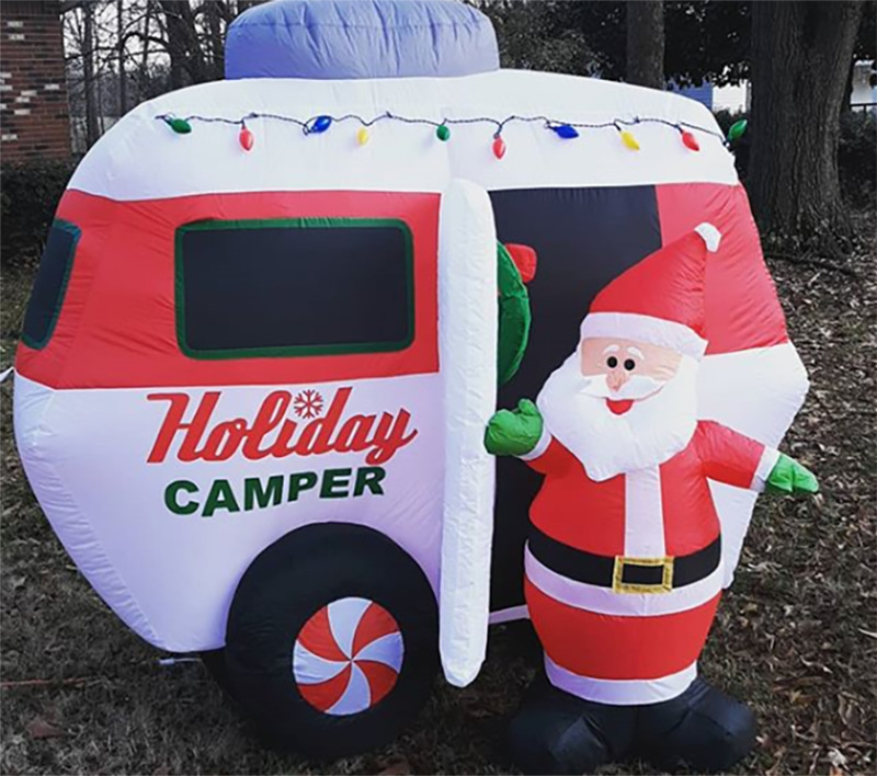 A blow up Santa Claus and camper sit in a front yard.