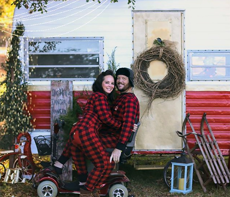 A couple in pajamas poses on a mobility chair in front of an RV.