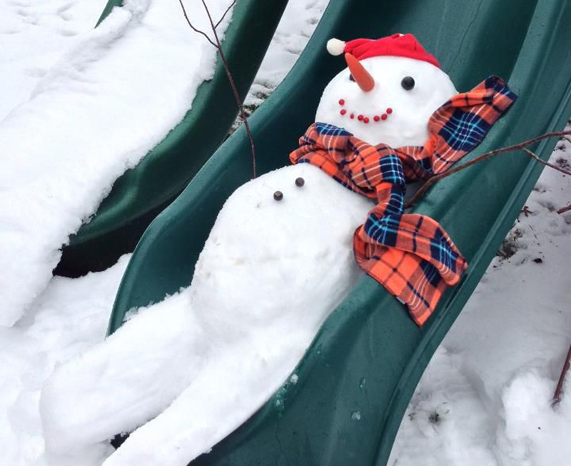 A snowman plays on a slide.