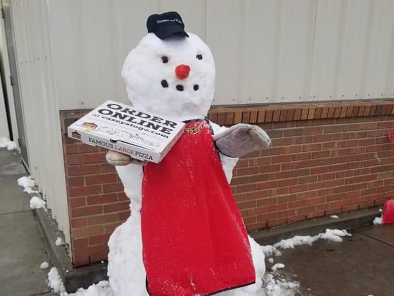 A pizza snowman holds a pizza box outside of a restaurant in Livington.