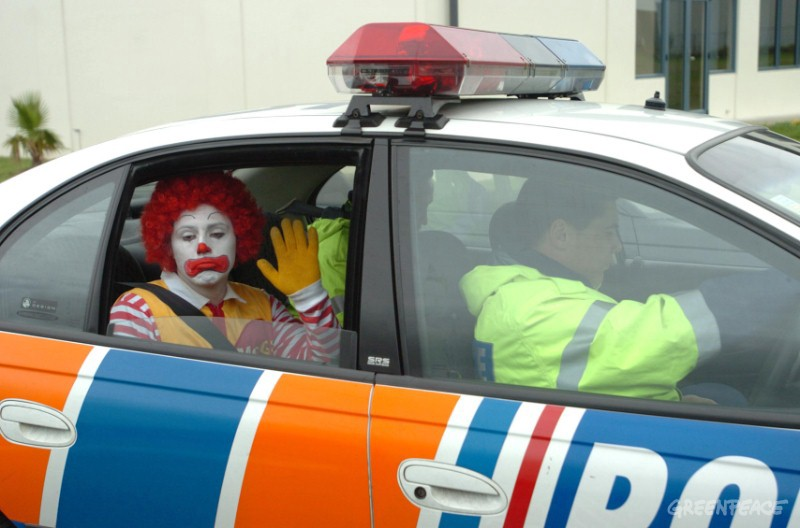 Some dressed as the McDonalds clown frowns and waves from the back of a cop car.