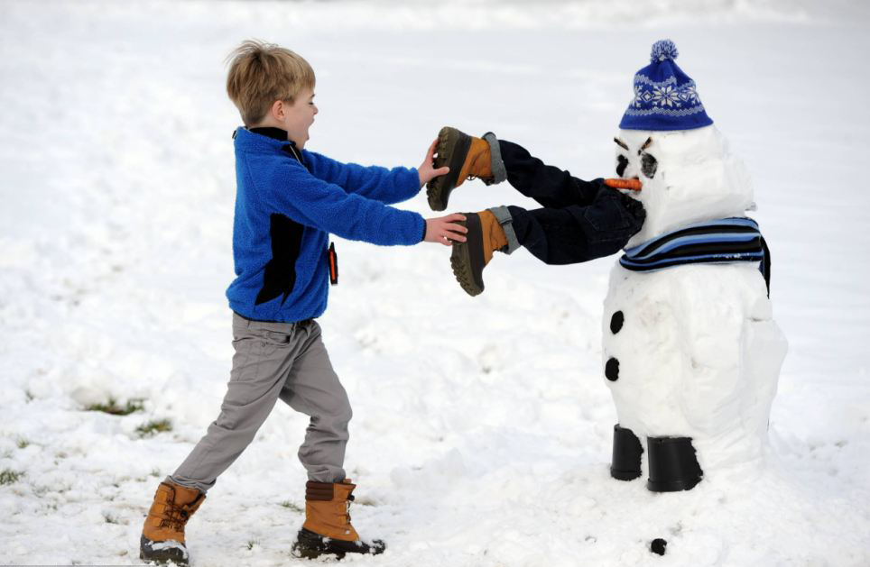 A boy grabs onto legs that seem to be in a snowman's mouth.