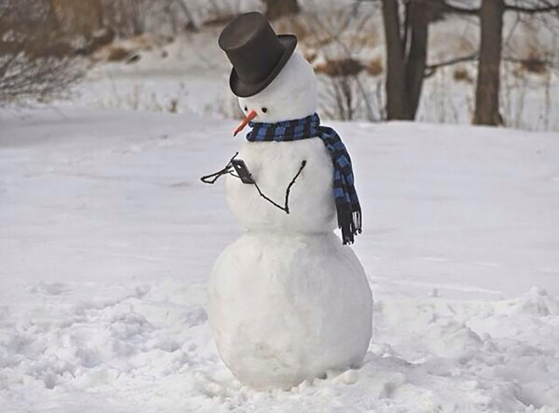 A snowman is posed as if it's scrolling through its phone.