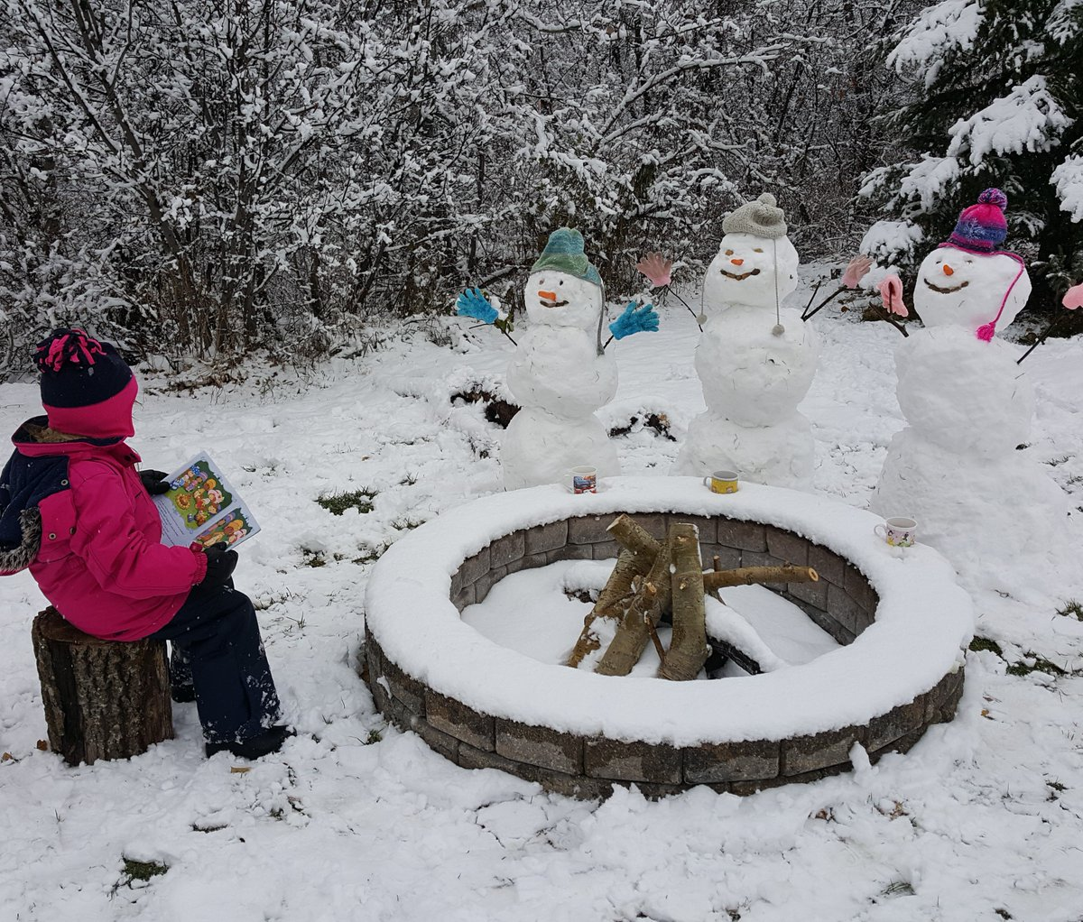 A child reads to snowmen gathered around a firepit.