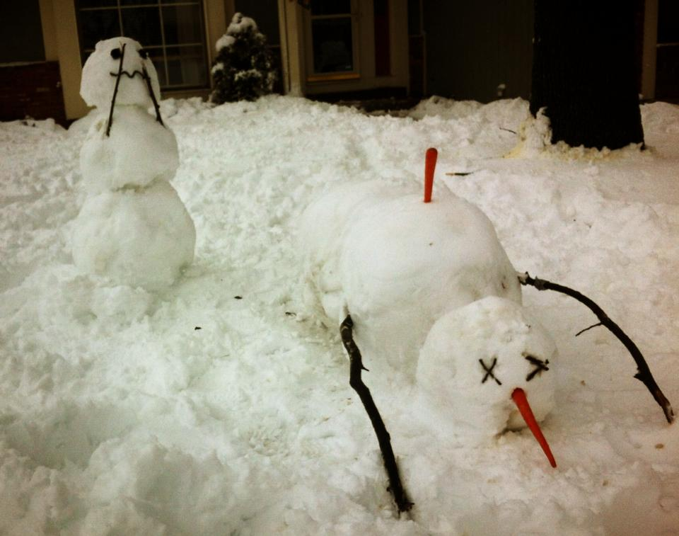 One snowman seems to have sneezed its carrot nose into another snowman's back.