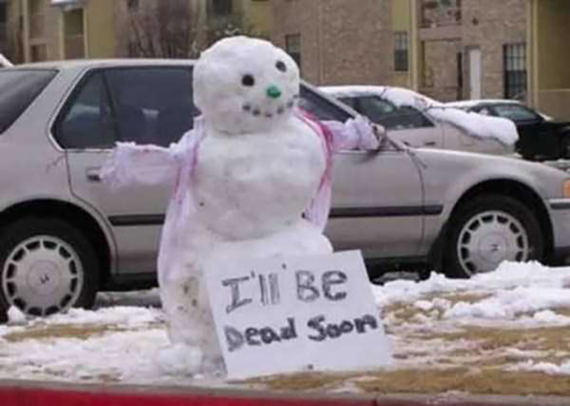 A snowman holds a sign that says