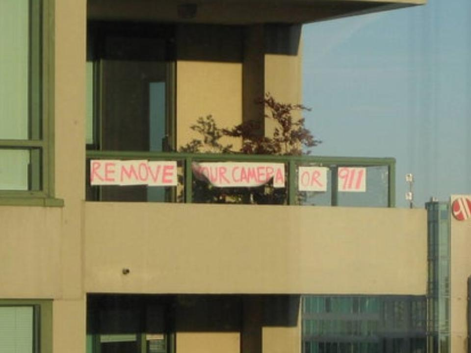 A makeshift banner hanging on a high rise balcony reads