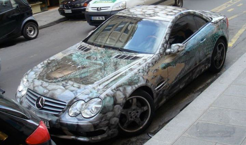 A Mercedes Benz is covered in the image of rocks and alligators.