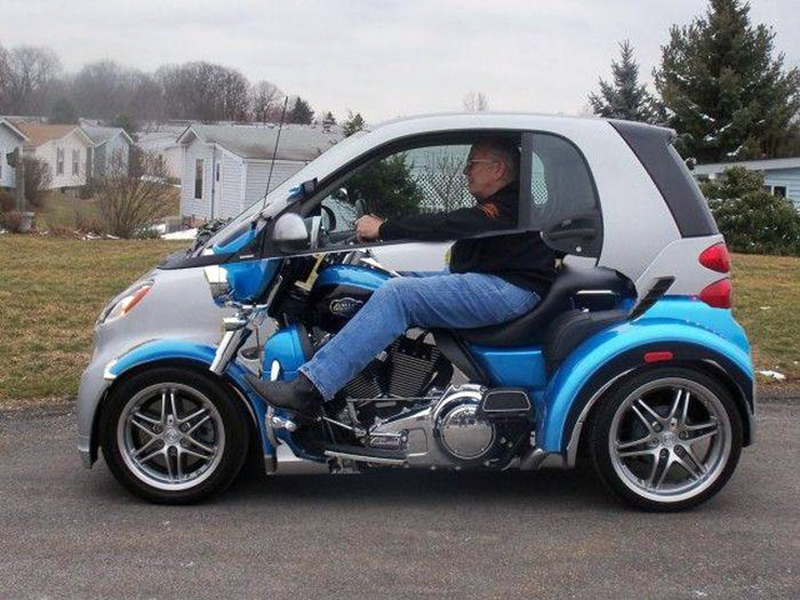 A smart car has the optical illusion paint job so that the driver appears to be driving a motorcycle.