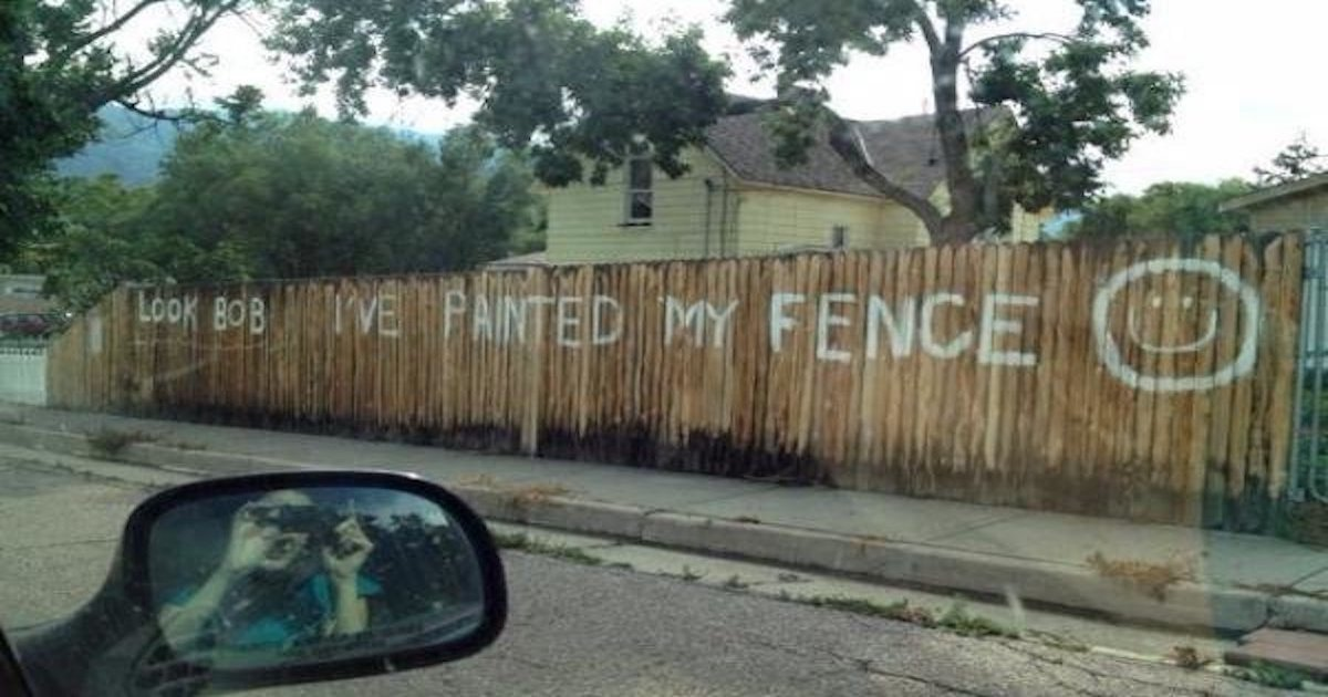 An old fence is painted with the words