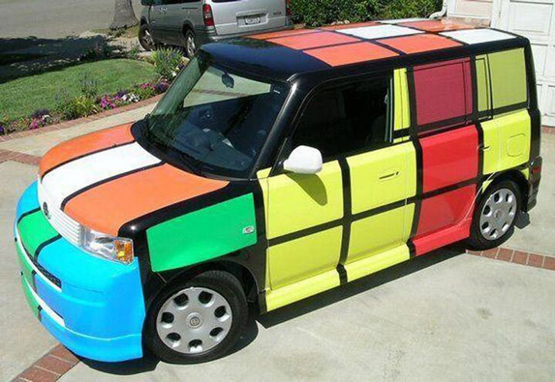 A box-shaped car is painted like a Rubik's cube.