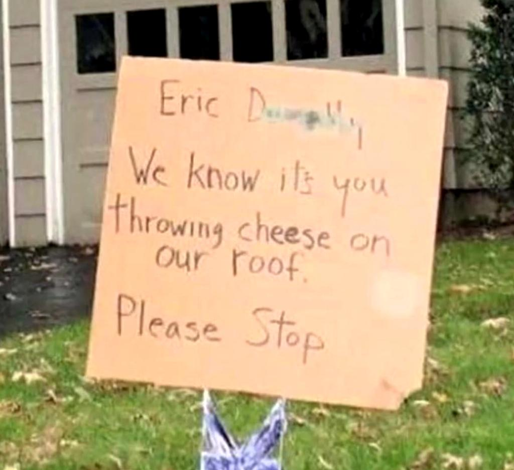 A sign asks a neighbor to stop throwing cheese on the roof.