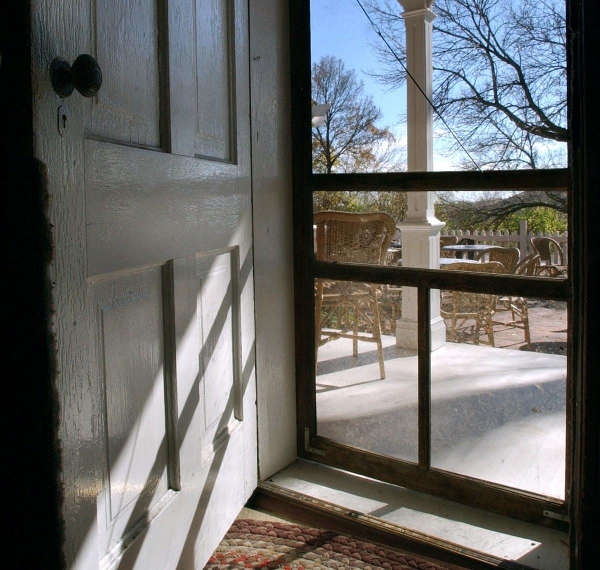 A front door is open to a screen door.