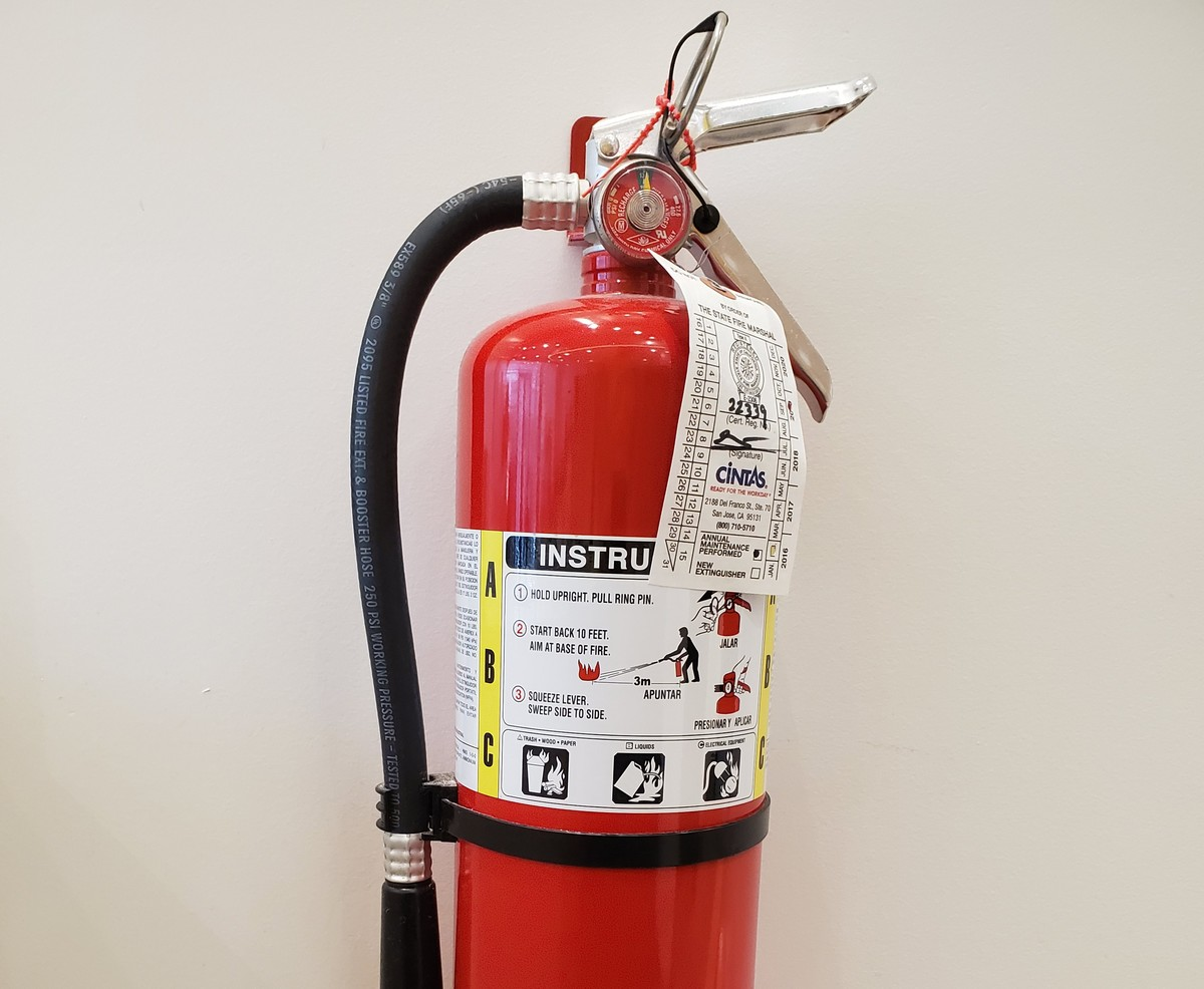 A fire extinguisher is mounted to a wall.
