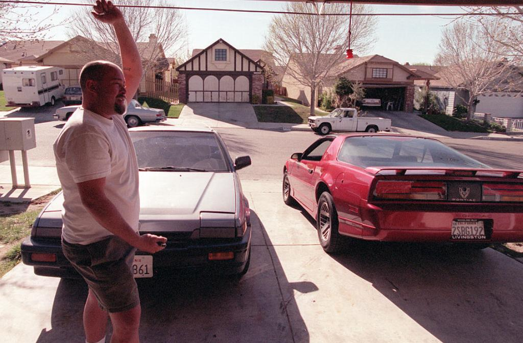 A man stands before his opened garage.