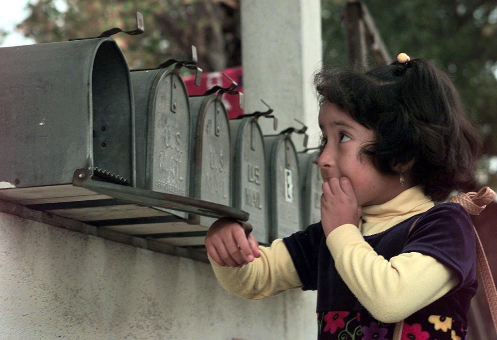A young girl checks a mailbox that's one of several identical mailboxes in a row.
