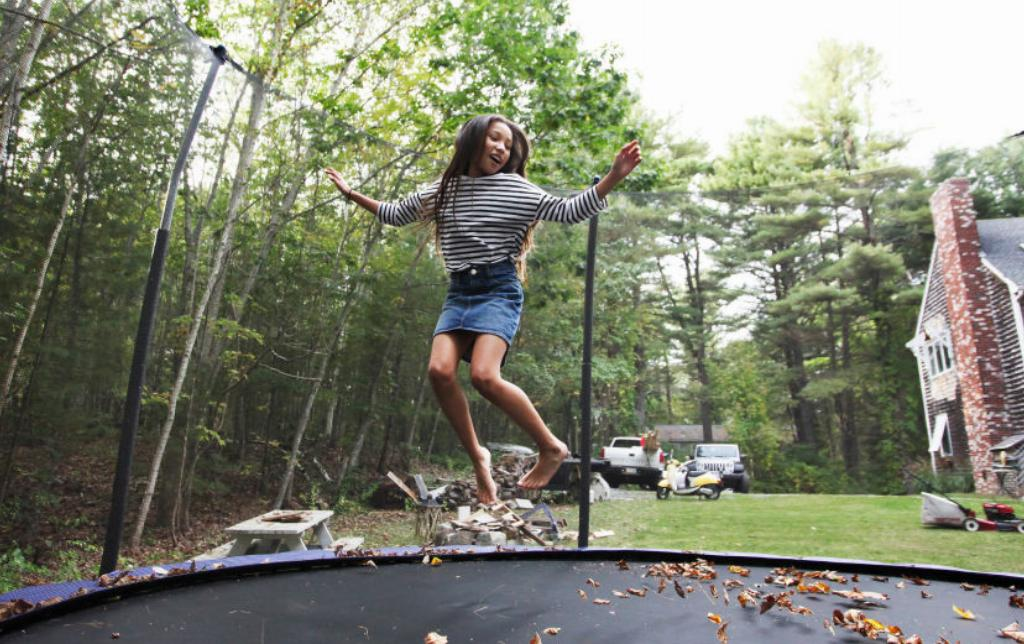 A girl jumps on a trampoline.