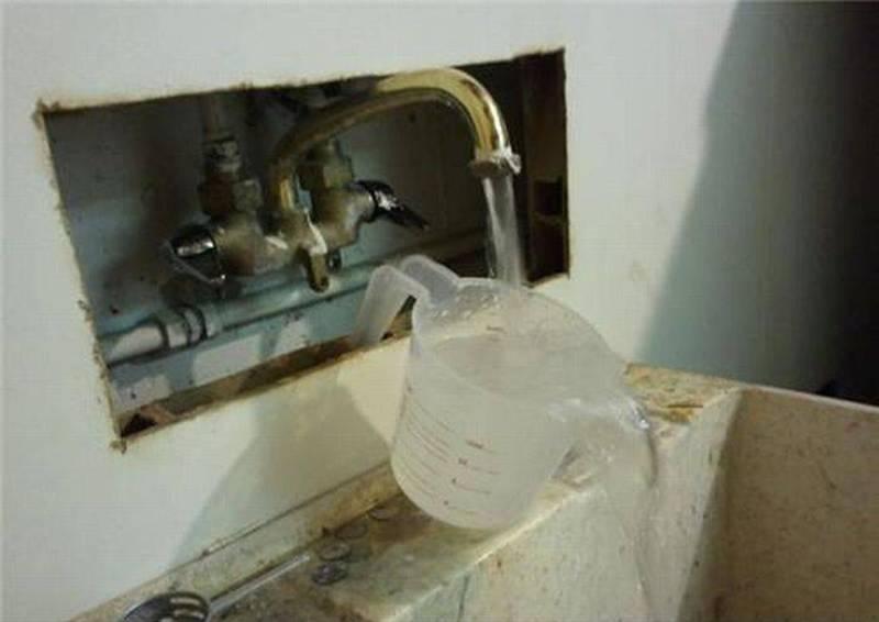 A faucet pours into a measuring cup which pours into a drain.