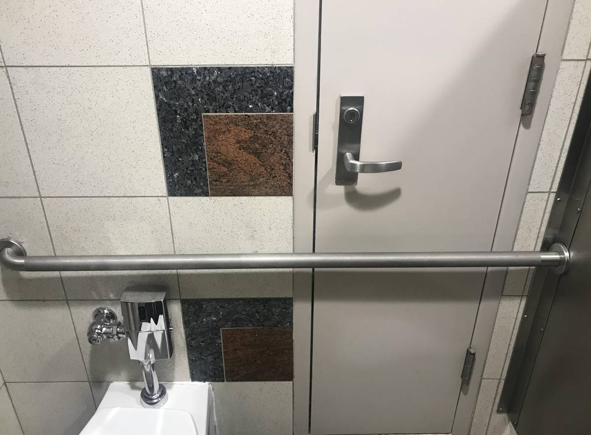 A door is trapped behind a horizontal pole in an airport restroom.