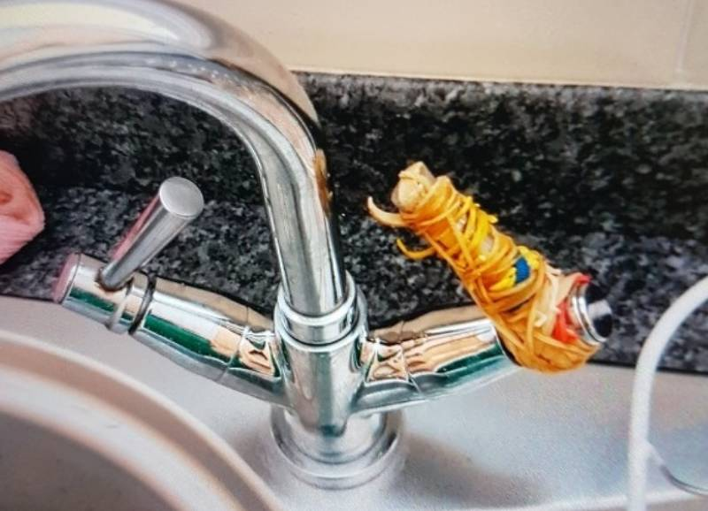 A sink tap is covered with rubber bands.
