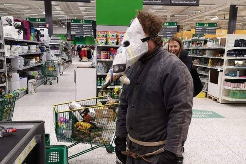 A man shops in a plague doctor mask made out of newspaper.