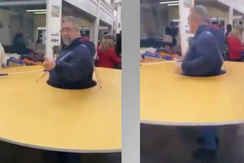 A man strapped a circular table around himself to keep others six feet apart.