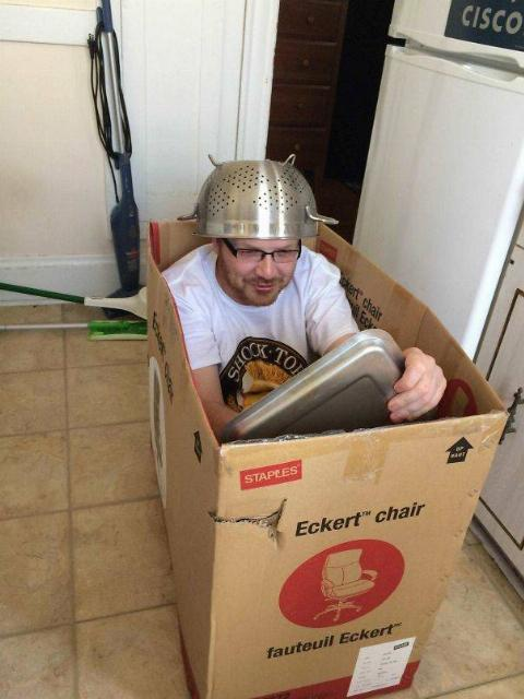 a man sitting in a cardboard box with a pot on his head