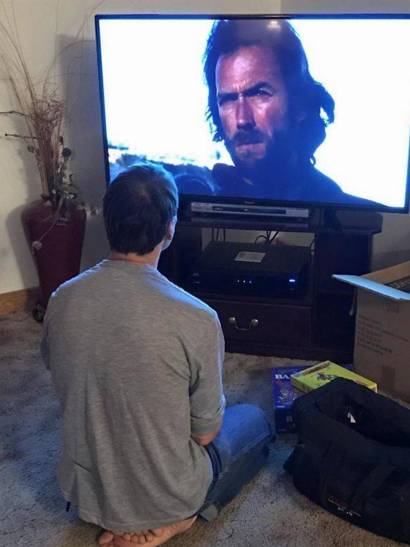 man sitting cross-legged while watching a clint eastwood movie