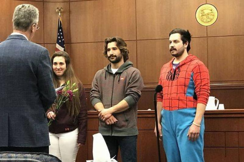 a man dressed as spider-man with a couple getting married in a courthouse
