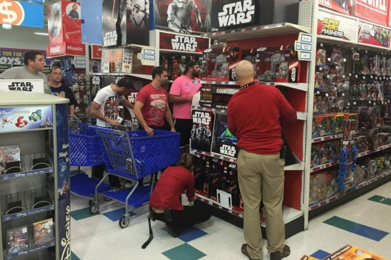 a group of men in a store looking at star wars toys